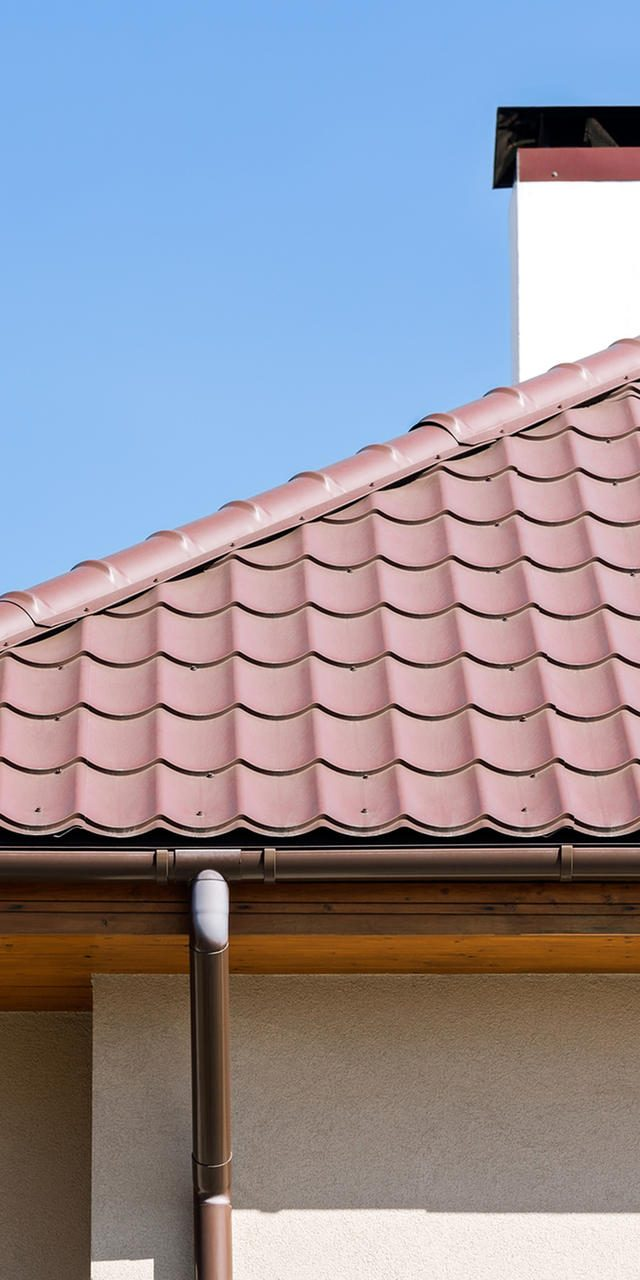 Corner of a house with gutter and tiled roof